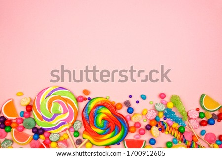 Colorful sweet candies. Above view bottom border on a pink background. Stock foto ©