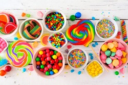 Colorful sweet candy buffet table scene. Top view over a white wood background.