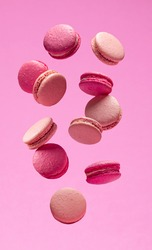 Colorful sweet macarons or macaroons, flavored cookies floating in the air on pink background.