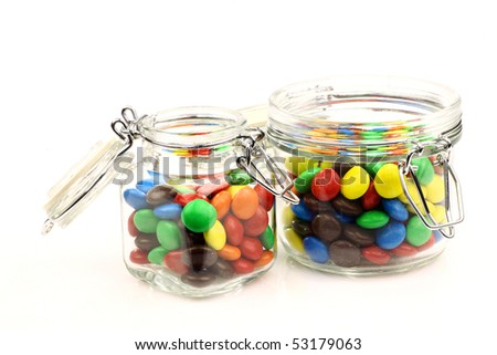 colorful sweets in a glass jars on a white background