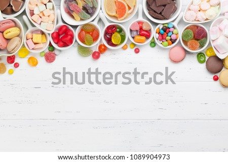 Colorful sweets. Lollipops, macaroons, marshmallow, marmalade, chocolate and candies. Top view with space for your greetings