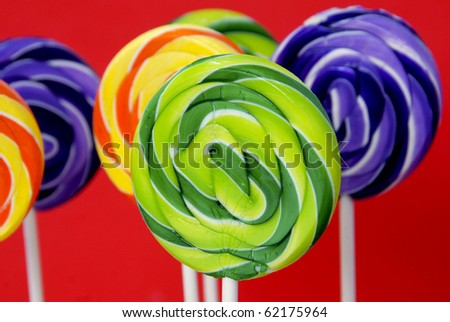 Colorful swirled lollipops on a red background