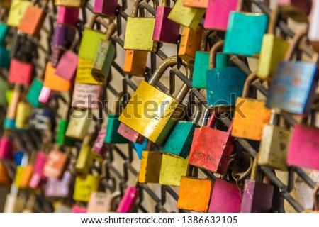 Colorful symbolic couple love padlocks attached to railings. Valentine's day concept #1386632105