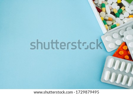 Photo of colorful tablets and capsules in a white box, tablets in a package, are located around the perimeter of the image with a free left and center under the text on blue background, isolated