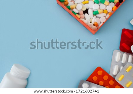 Photo of colorful tablets and capsules in an orange box, bottle, container, tablets in a package, are located around the perimeter of the image with a free left and center under the text on blue background