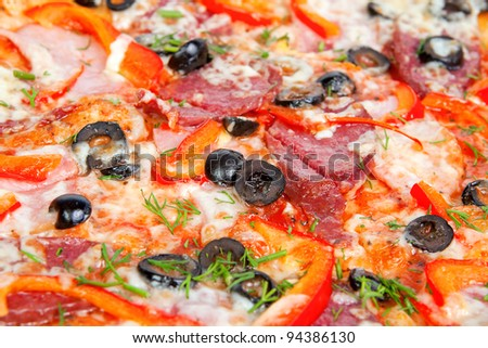 colorful tasty pizza with olives, pepperoni, ham and pepper, close-up shot
