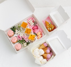 Colorful tasty sweets in opened white windowed boxes. Zefir, cookies, macarons and cakes decorated with branches and flowers. Top view.