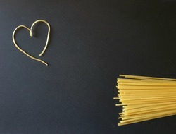 Colorful template for cooking topics. A pile of raw spaghetti on one side and a heart shape drawn with a noodle. Background image for presentations, powerpoint, seminars. Useful for recipe concepts.