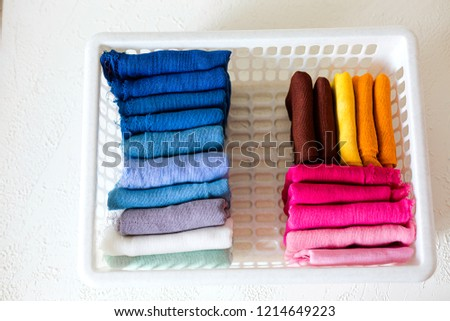 Colorful textile on white background. Keeping clothes in a wardrobe or on market shelves. Cotton, copy space. #1214649223