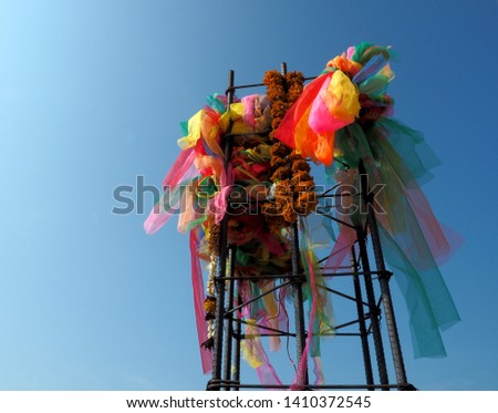 Colorful textiles are used for a ceremony at a new construction site.  Thais wish & pray for prosperity, good luck through this religious rituals as a cultural belief. Blue sky in background.