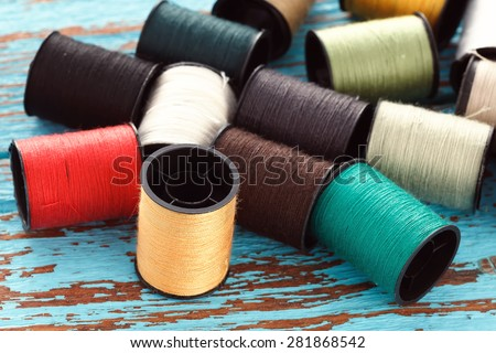 colorful thread needlework embroidery tailor craft repair background blue wood teak still life vintage
