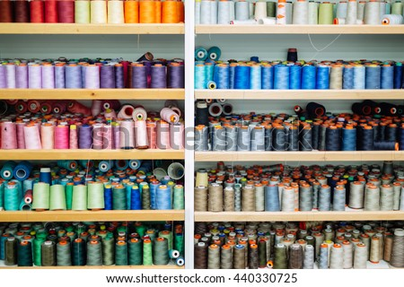 Colorful thread spools used in fabric and textile industry #440330725