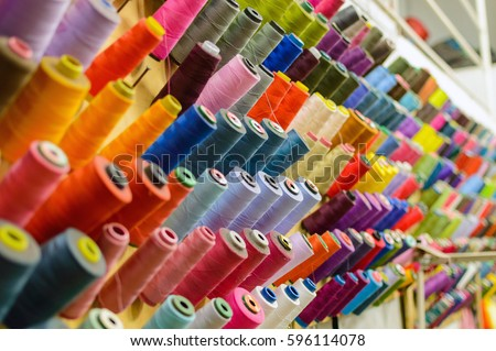 Colorful thread spools used in fabric and textile industry. The concept of sewing production. #596114078