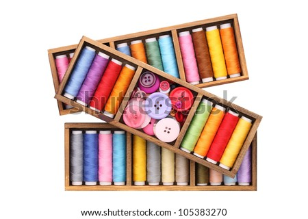 Colorful threads and buttons in wooden box