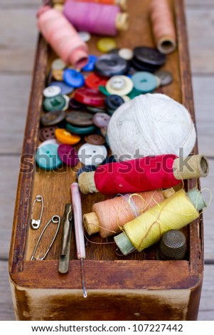 Colorful threads and old scissors on the old wooden table/Old sewing accessories