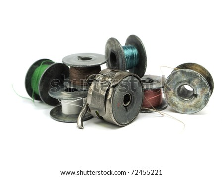 Colorful threads vintage spools and sewing machine items on a white background
