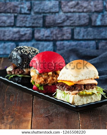 Colorful three mini burgers served on black plate as appetizer. Delicious classic, black and pink slider burgers loaded with beef patty, crispy chicken, lettuce, coleslaw, cheese, mushrooms. Image