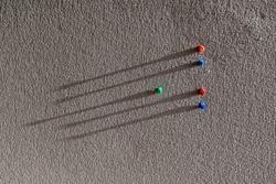 Colorful Thumb Tacks on Gray Board With Long Shadows