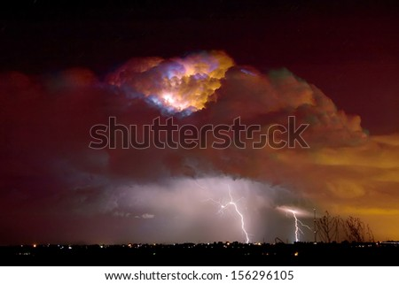 Colorful thunderstorm thunderhead lit up with lightning bolts striking in Boulder County Colorado.
