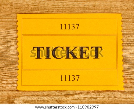 Colorful ticket on wooden background close-up