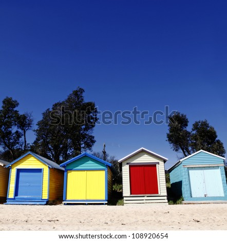 Colorful timber beach hut on a sandy beach on a clear summer day.
