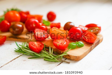 Colorful tomatoes on board on wooden background  #181093940