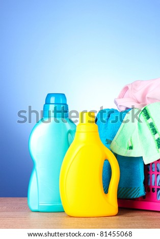 Colorful towels and liquid laundry detergent   over blue