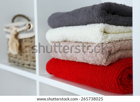 Colorful towels with wicker basket on shelf of rack background #265738025
