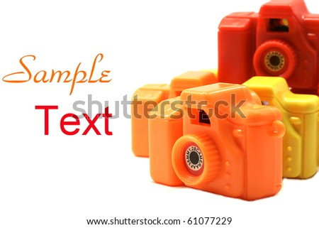 Colorful Toy Cameras on white back background with copy space.  Macro with extremely shallow depth of field.