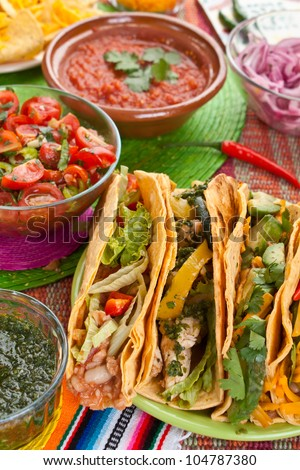 Colorful Traditional Mexican food dishes: various fajitas, nachos, salsa verde, tomato salsa, salsa cruda served on a beautifully decorated table