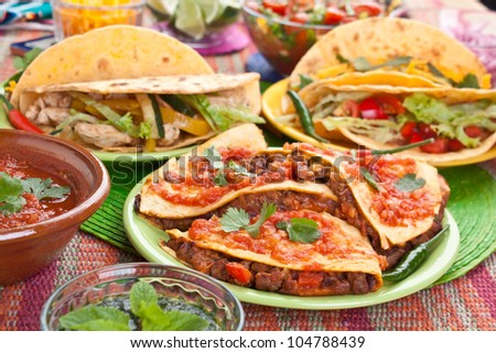 Colorful Traditional Mexican food dishes: various fajitas, quesadillas, salsa verde, tomato salsa, salsa cruda served on a beautifully decorated table