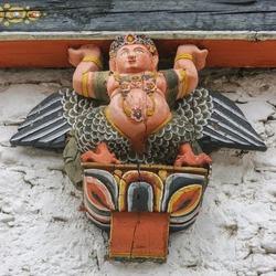 Colorful traditional painted kinnara - half bird half human - wood sculpture used as corbel in Tashichho dzong in Thimphu, Bhutan