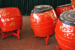 Colorful traditional red and gold painted barrel drums on dark tile floor inside a Buddhist temple in Vietnam