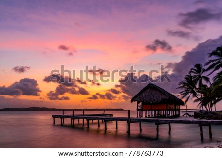 Stock Photo Colorful tropical sunset on one of the San Blas islands in the Caribbean Sea. Shore scene with a beach house and a jetty.