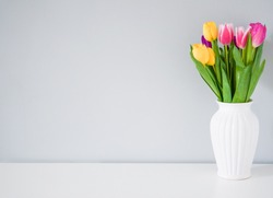 Colorful tulips in white vase on the table on light grey background