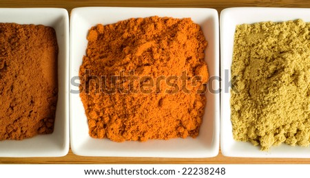 Colorful tumeric, cayenne pepper and cloves powder spices in square brown dishes