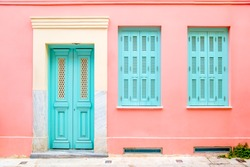 Colorful turquoise blue door and windows in a pink wall.