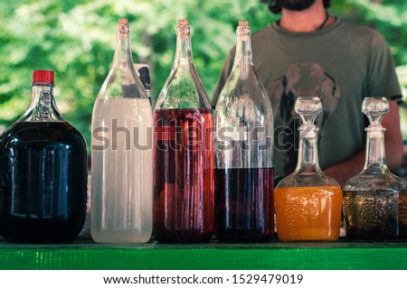 Colorful Ukrainian man with a beard sells home-made alcohol outdoors near Shipot waterfall. Beautiful glass bottles of different shapes and sizes.