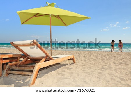Colorful umbrella and lounge chair in the trendy and popular South Beach in Miami with young bathers in the background. #71676025