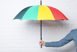 Colorful umbrella in male hand on brick wall background