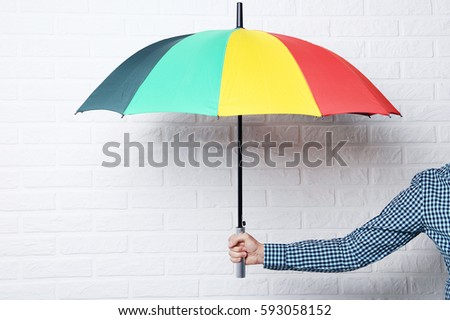 Colorful umbrella in male hand on brick wall background #593058152