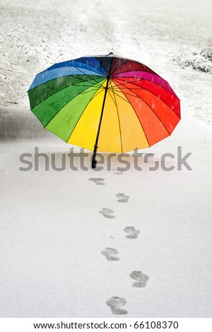 Colorful umbrella in the fresh snow with some footprints around it.
