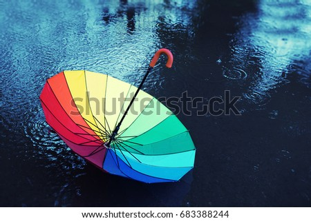 colorful umbrella in the rain. the umbrella is lying on the street in the rain in  puddle . Soft focus #683388244