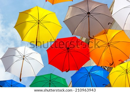 Colorful umbrellas against the sky in city settings. Umbrellas provide summer shade and attraction for shopping district.