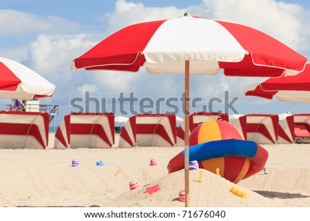 Colorful umbrellas and lounge chairs in the trendy and popular South Beach in Miami.