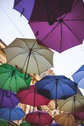 Colorful umbrellas hang against the blue sky. High quality photo