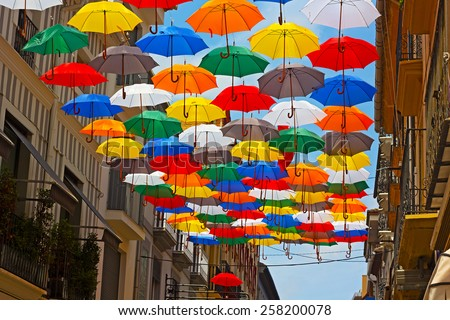 Colorful umbrellas installed on the street in Spanish city. Urban sun protection with umbrellas at work.
