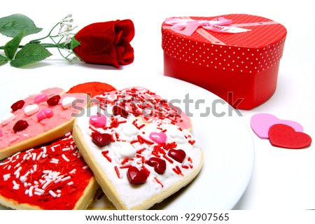 Colorful Valentines Day cookies on a plate with gift box and rose over white