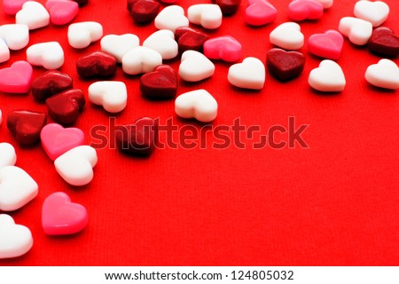 Colorful Valentines Day heart shaped candy border on red paper background