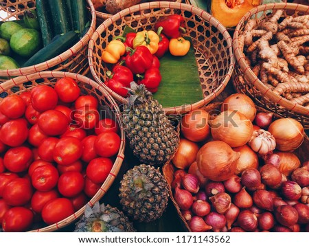 colorful vegetable fruit turmeric tomato pineapple onion shallot red yellow Bell pepper lemon on banana left in basket in market for cooking food manufacture  medicine make people healthy younger #1171143562